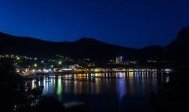 Sikten av den Black Sea fjärden mellan berg med stadsljus reflekterar Arkivfoto