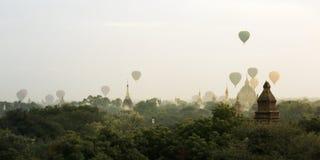 Sikten av den buddistiska templet, stupa, i det historiskt parkerar av Bagan, med luftballongen i himlen royaltyfri fotografi