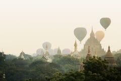 Sikten av den buddistiska templet, stupa, i det historiskt parkerar av Bagan, med luftballongen i himlen royaltyfri bild