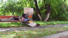 Sikten av den gamla tiggaren som sover på bänken i stad, parkerar arkivfilmer