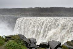 Sikten av den kraftiga Detifoss vattenfallet med gräs och vaggar på Arkivbilder