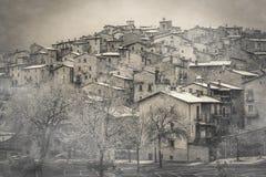 Sikten av den mystiska medeltida byn med dimma och den insnöade vintern kryddar, Abruzzo Royaltyfria Bilder