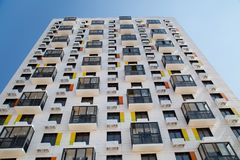 Sikten av den nya härliga vita hyreshusen med orange brytningar, försåg med gångjärn glasade balkonger royaltyfria foton