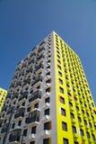 Sikten av den nya härliga vita hyreshusen med orange brytningar, försåg med gångjärn glasade balkonger arkivfoton