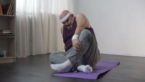 Sikten av den roliga överviktiga mannen som gör hemmastadd som yoga försöker att sitta i lotusblomma, poserar lager videofilmer