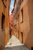 Sikten av den smala gatan och byggnader med shoppar i Grasse Fotografering för Bildbyråer