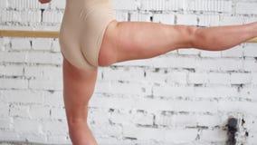Sikten av det kvinnliga dansareanseendet på ett ben och fördjupa upp annat i ljust rum stock video
