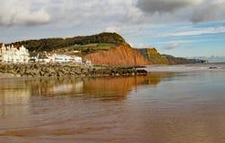 Sikten av easten slutet av den Sidmouth promenaden och sandstenklippan Denna klippa har vanliga rockfalls som förminskar längdern arkivfoton