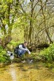 Sikten av en biolog tar en prövkopia i en flod Royaltyfria Bilder