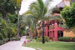 Sikten av en tropisk semesterort med palmträd, går banan och färgrika bungalower Arkivbild