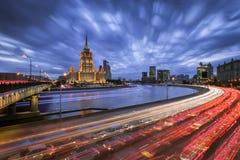 Sikten av hotellet Ukraina med snabba springmoln och ljusa lastbilar strömmar Royaltyfri Bild