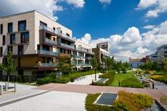Sikten av offentligt parkerar med det nybyggda moderna flerbostadshuset Royaltyfria Foton