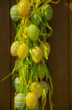 Sikten av påskgarnering med gräsplan och guling målade ägg Royaltyfri Foto