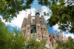 Sikten av Sagrada Familia från gräsplan parkerar och träd Royaltyfri Fotografi