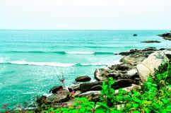 Sikten av sandstranden och havet vinkar med vaggar och molnigt på eftermiddag royaltyfria foton