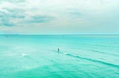 Sikten av sandstranden och havet vinkar med vaggar och molnigt på en eftermiddag royaltyfria bilder