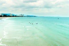 Sikten av sandstranden och havet vinkar med vaggar och molnigt på en eftermiddag royaltyfri bild