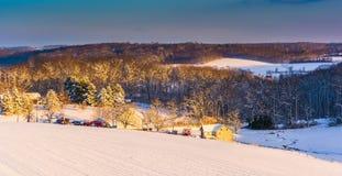 Sikten av snö täckte lantgårdfält och Rolling Hills på solnedgången in fotografering för bildbyråer