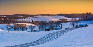 Sikten av snö täckte Rolling Hills och lantgårdfält på solnedgången in arkivbild