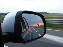 Sikten av solnedgången i Wien reflekterade i bilspegel Arkivfoton