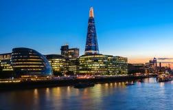 Sikten av stadshuset för London ` s och moderna skyskrapor på natten Royaltyfri Bild