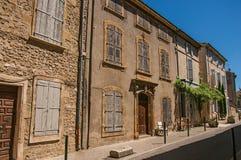 Sikten av typiska stenhus och shoppar på en gata av Lourmarin Arkivbild