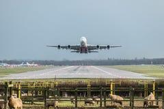 Sikten direkt ner landningsbanan som en emiratflygbolagnivå tar av från den London Gatwick flygplatsen som går mot Dubai royaltyfri foto