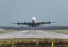 Sikten direkt ner landningsbanan som en emiratflygbolagnivå tar av från den London Gatwick flygplatsen som går mot Dubai royaltyfri fotografi