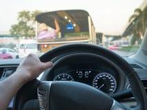 Sikten för bilen ombord av den hållande styrningen för handen rullar in bilen Arkivbild