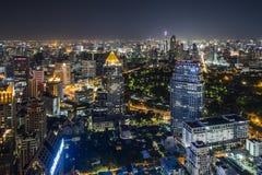 Sikten för den Bangkok cityscapenatten av affärsområdet och lumpinien parkerar Arkivbild