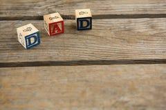 Sikten för den höga vinkeln av kuben formar med farsatext och nummer på tabellen Royaltyfri Fotografi
