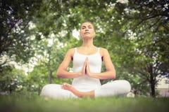 Sikten för den låga vinkeln av den härliga kvinnan med stängda ögon, medan sitta i lotusblomma, poserar Royaltyfri Foto