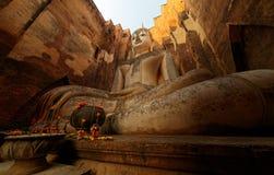 Sikten för den låga vinkeln av en jätte- forntida Buddhastaty i templet Wat Si Chum i historiska Sukhothai parkerar, Thailand Royaltyfri Fotografi
