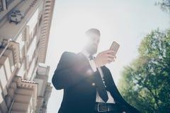 Sikten för den låga vinkeln av en ung affärsman i en flott dräkt kontrollerar hans schema vid pda på gatan på den soliga sommarda arkivbilder