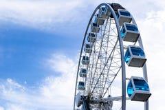 Sikten för den låga vinkeln av ferris rullar in ett nöjesfält med en bakgrund för blå himmel Staden parkerar ferris rullar in kar Royaltyfri Fotografi