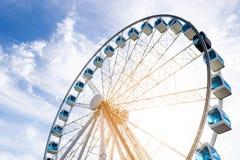 Sikten för den låga vinkeln av ferris rullar in ett nöjesfält med en bakgrund för blå himmel Staden parkerar ferris rullar in kar Arkivfoto