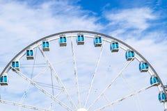 Sikten för den låga vinkeln av ferris rullar in ett nöjesfält med en bakgrund för blå himmel Staden parkerar ferris rullar in kar Arkivbild