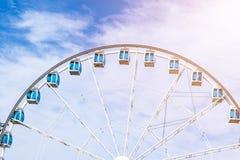 Sikten för den låga vinkeln av ferris rullar in ett nöjesfält med en bakgrund för blå himmel Staden parkerar ferris rullar in kar Arkivfoton
