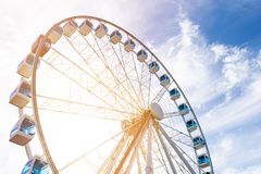 Sikten för den låga vinkeln av ferris rullar in ett nöjesfält med en bakgrund för blå himmel Staden parkerar ferris rullar in kar Royaltyfria Foton