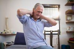 Sikten för den låga vinkeln av högt manligt tålmodigt sammanträde med halsen smärtar på säng Royaltyfri Bild
