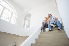 Sikten för den låga vinkeln av par med målning bearbetar sammanträde på moment i nytt hus Royaltyfri Foto
