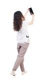 Sikten för den tillbaka sidan av en kvinna som går med en minnestavlaPC, är i hanen Royaltyfria Bilder