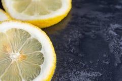 Sikten för närbilden av skivor av citronen på våt svart stenar överst bakgrund royaltyfri bild