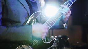 sikten för närbilden 4k av mannen räcker att spela gitarren med en medlare Gitarristen utför på etapp lager videofilmer