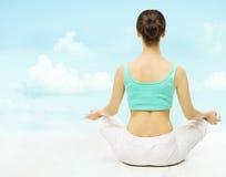 Sikten för yogakvinnabaksida mediterar sammanträde i lotusblomma poserar över himmelbac Arkivbild