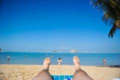 Sikten från ögonen av en man, som ligger på sanden och ser ut på havet, och dig kan se hans fot Royaltyfri Bild