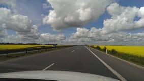 Sikten från bilen på väghimmel fördunklar och blommar Arkivbild