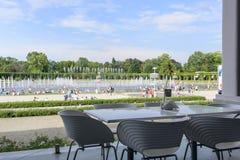 Sikten från den tomma restaurangen på folk som kyler genom att använda offentliga springbrunnar i den varmmaste dagen på 19 Juli  Royaltyfri Bild