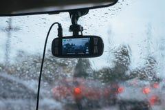 Sikten från digital kamera inom bilfönster med regn tappar på exponeringsglas eller vindrutan, suddig trafik på regnig dag royaltyfria bilder