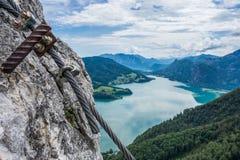 Sikten från Drachenwand vaggar på Mondsee och Attersee Via ferrata i den Halstatt regionen Österrike Ett stålrep fästas till vagg Royaltyfria Bilder